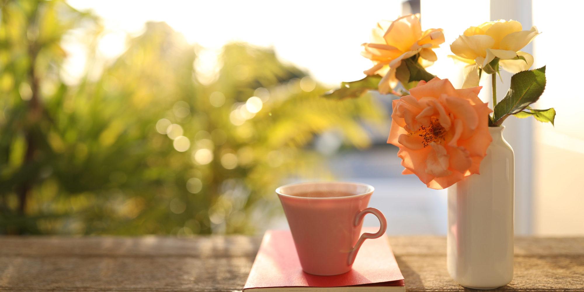 Rosa Tasse auf einem roten Buch. Daneben eine Vase mit hellen Rosen. Im Hintergrund ist durch grüne Bäume ein Sonnenaufgang zu erahnen.