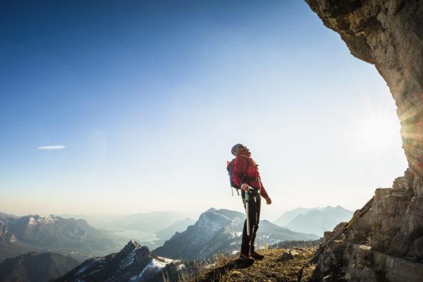 Wanderer steht am Felsen und schaut fragend hoch