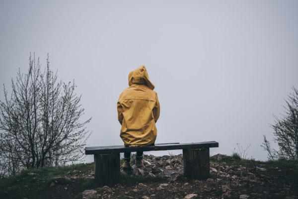 Person sitzt mit gelber Regenjacke auf einer Holzbank. Überall Nebel.
