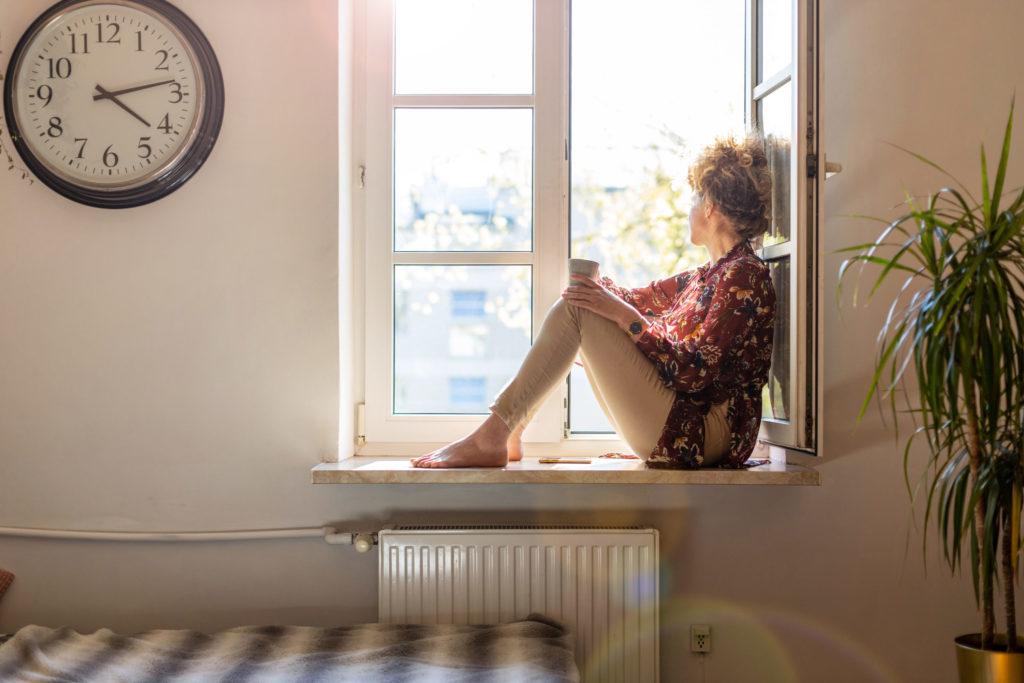 Frau sitzt mit Tasse im offenen Fenster. Neben ihr eine große Wanduhr
