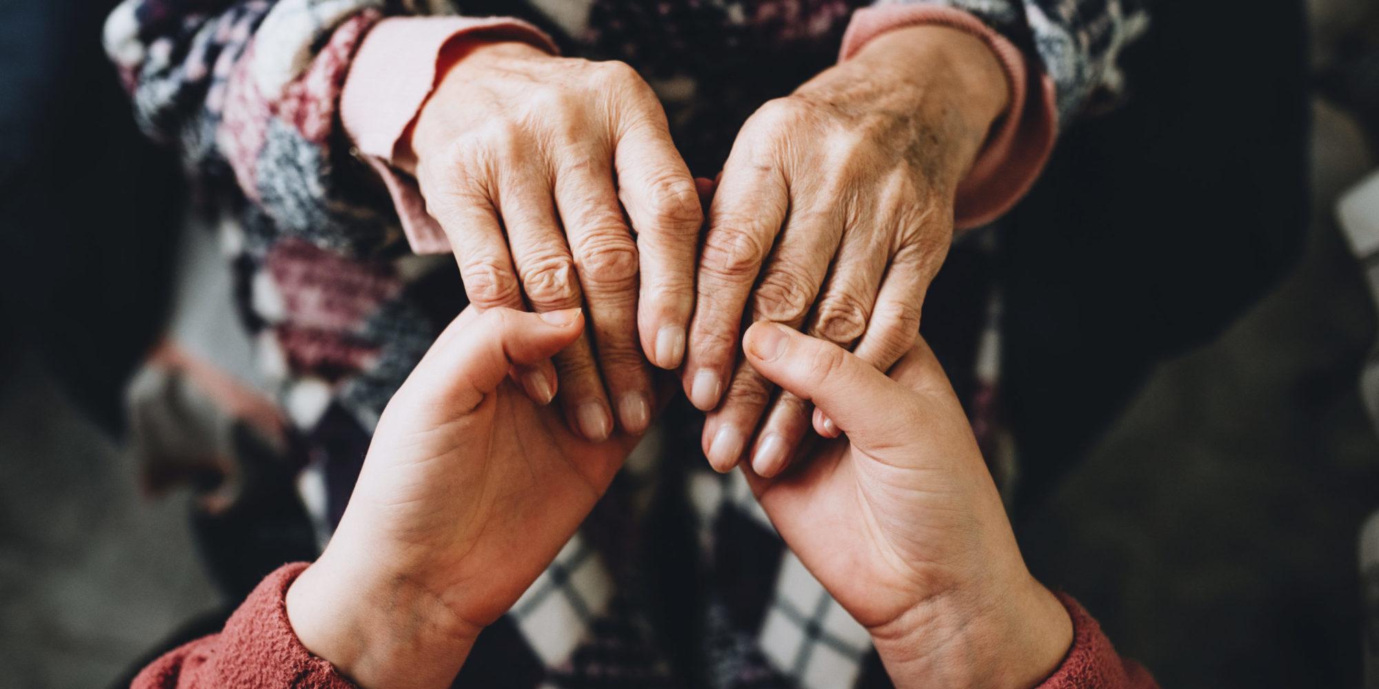 Zwei Menschen legen ihre Hände ineinander