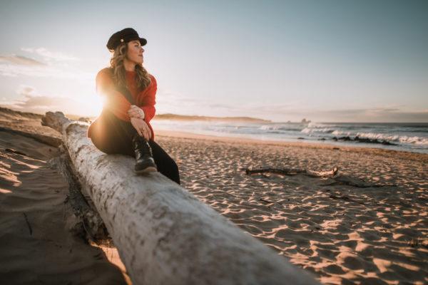 Frau sitzt auf Baumstamm am Strand